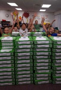 Photo of kids jumping up from behind tall stacks of chocolate boxes.